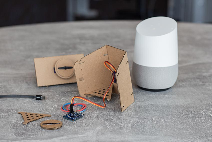 Cardboard pieces, electronic components, a Google Home and an assembled Domestic Widget