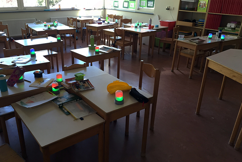 A classroom with a FireFly on each table, showing various colours on their top and bottom halves
