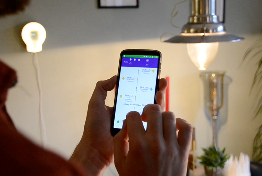 A person holding a phone with the app, with a light sensor in the background on the wall