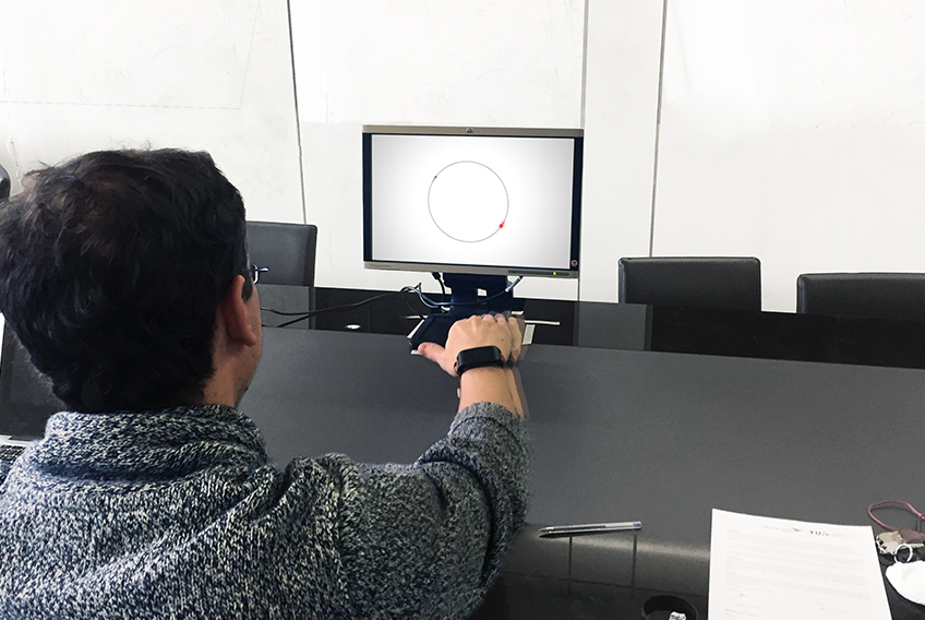 A person in front of a monitor, following a red dot